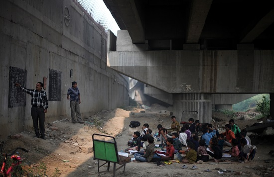Rajesh Sharma holds free classes for hundreds of slum children under the elevated tracks of the Yamuna Bank Metro station.