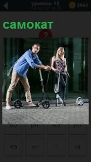 Девушка и парень катаются на самокатах по улице, пытясь научиться правильно пользоваться механизмом