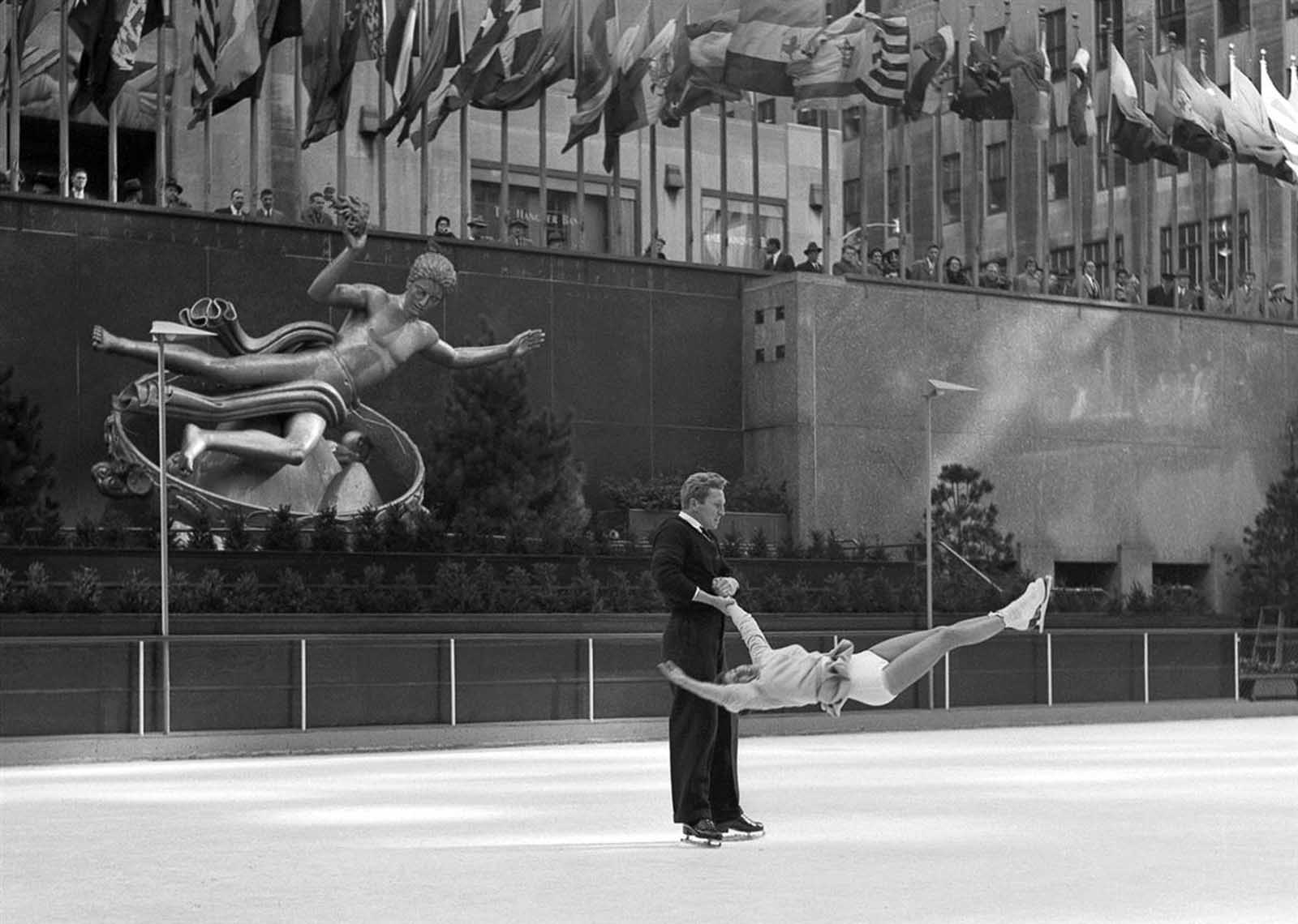 Professional skaters execute turn in mid-air, Rockefeller Center.