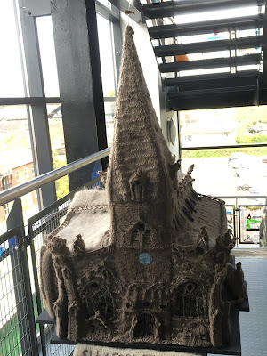 photograph of a model of a church, crafted from grey wool