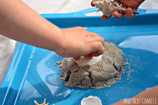 Stamping seashells into homemade sand dough