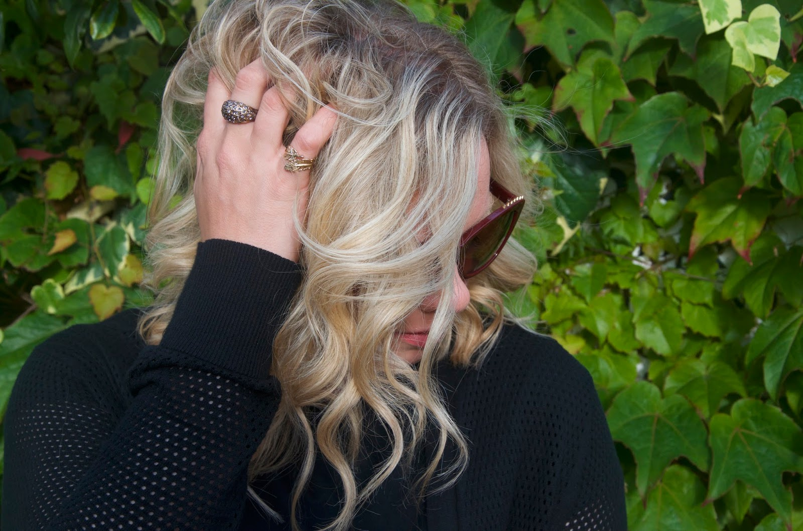 blonde hair, black net sweater and grey stone gold ring