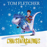The Christmasaurus audiobook review. A small boy in a colourful dressing gown rides a snow-white and blue dinosaur across a snowy, nighttime landscape.