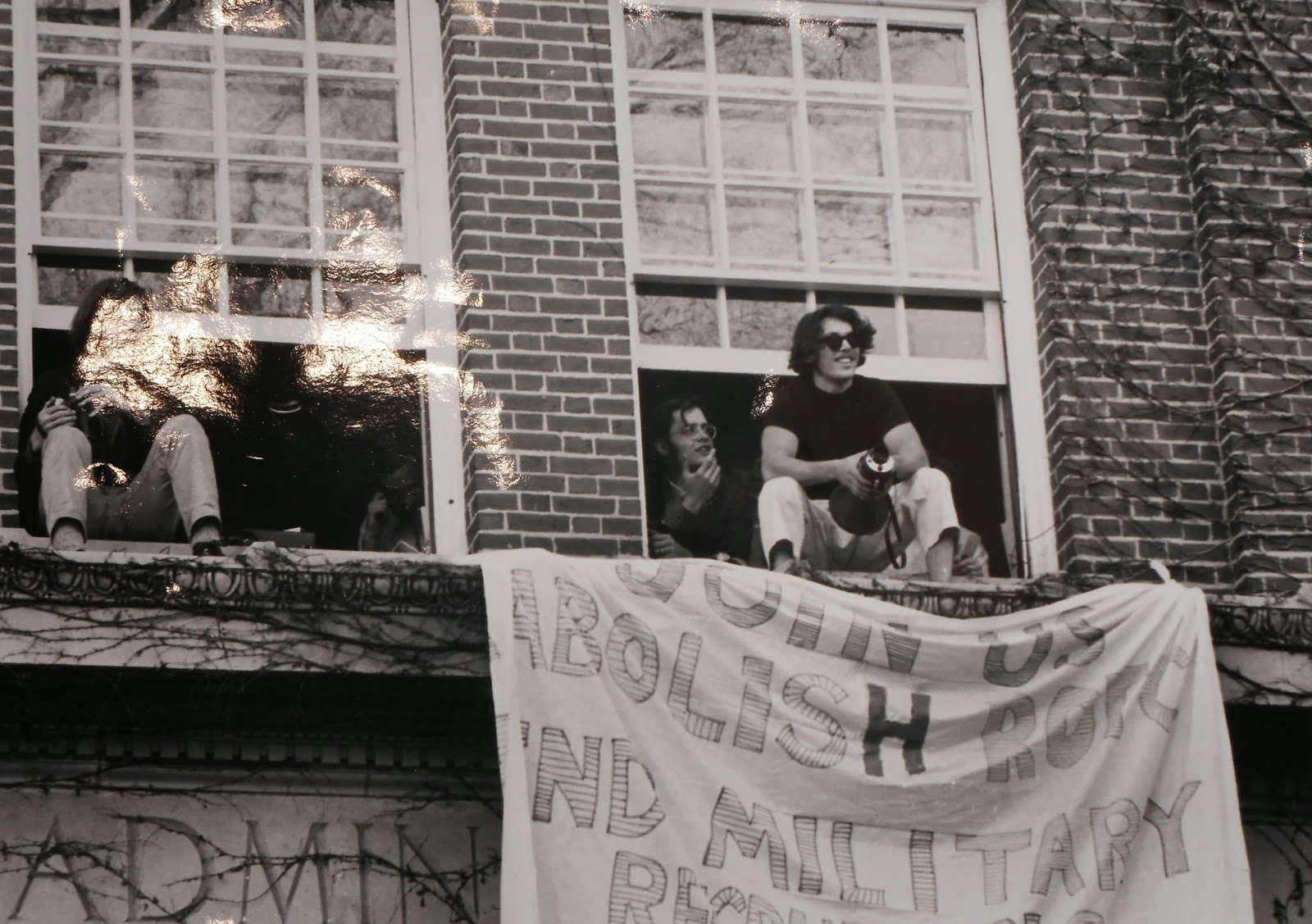 A black and white photograph of students perched in the open windows of an administrative building, out of which hangs a hand-made banner.