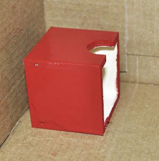 primera caja pintada de rojo, secando en una caja de cartón