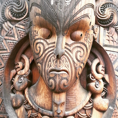 Close up of a maori carving of a face.