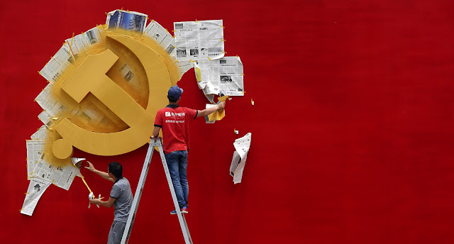 Workers peel papers off a wall as they re-paint the Chinese Communist Party flag on it at the Nanhu revolution memorial museum in Jiaxing, Zhejiang province May 21, 2014. REUTERS/Chance Chan via GIGA Hamburg