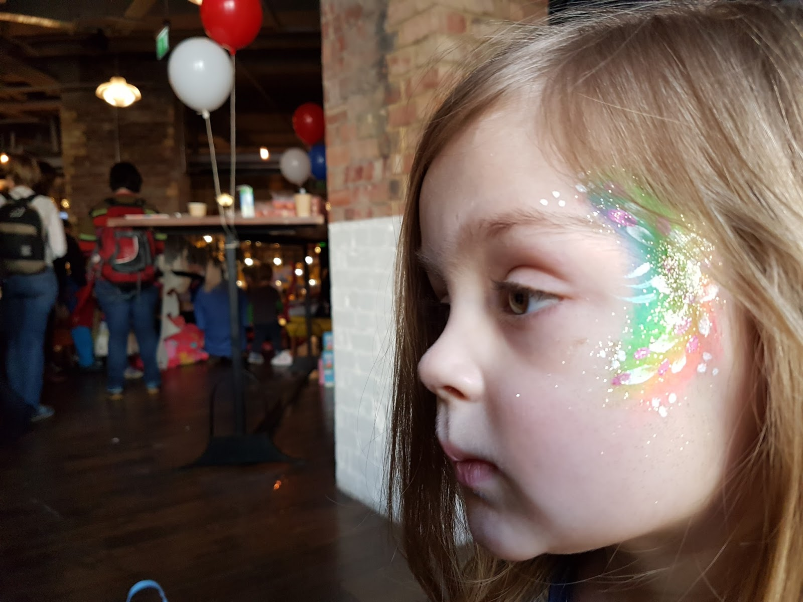 little girl with a rainbow face painting