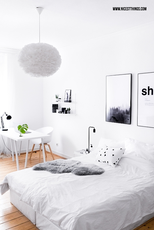 Schlafzimmer weiss mit Holzdielen und Boxspringbett