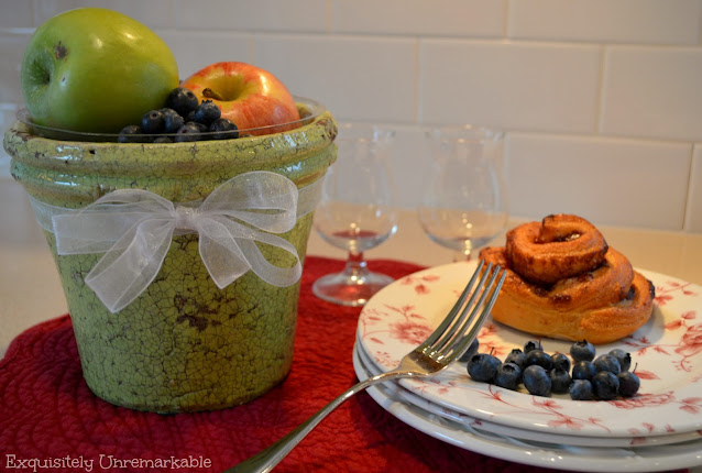 Flower pot fruit bowl filled with fruit next to a plate with fruit