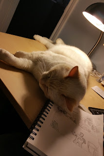 cat sleeping on top of graphic novel draft