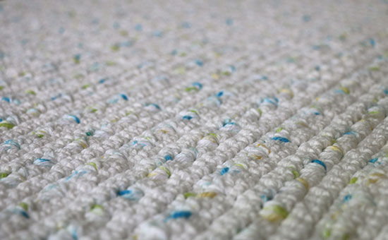 Alex Bath Mat Crochet Rug from an Angle in White with flecks of Yellow, Green and Blue