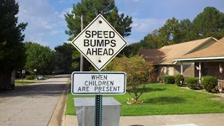 funny road sign children are speed bumps