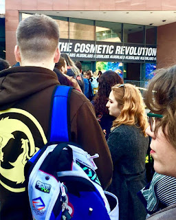 A long line of several people queuing including one person in a blue coat with a black backpack with a banner in front of them saying Welcome to the cosmic revolution in white font on a blue background