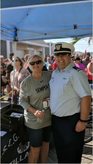 Auxiliarist Christopher Orlando (right) poses with a member of the general public at the Public Affairs booth after the Seaside Semper Fi 5K Charity Run.