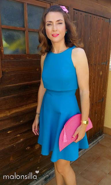 Look invitada comunión con vestido azul turquesa, bolso fucsia, buganvilla y rosa con horquillas de flores