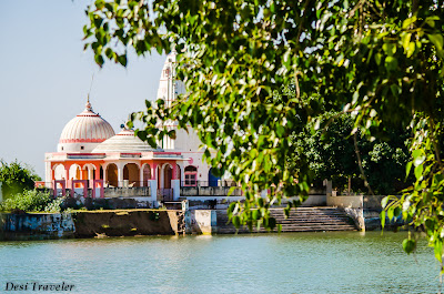 a hindu temple near a pond in a village in India