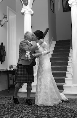 Bride and her Father embrace at the bottom of the wedding venue's staircase