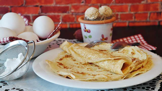 White plate with classic pancakes, eggs in a bowl and sugar in sieve