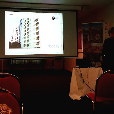 Rebecca Hawcroft giving a talk in front of a slide of the modernist Dixon Street Flats in Wellington.