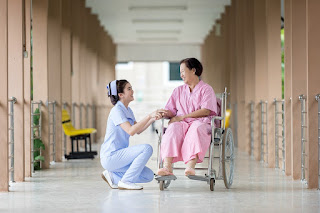 nurse and elderly woman in wheelchair