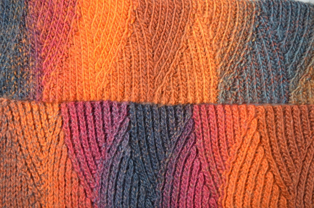 "Close-up of slip stitch scarf in ""Vesuvius"" colours (oranges, reds and charcoal greys)."
