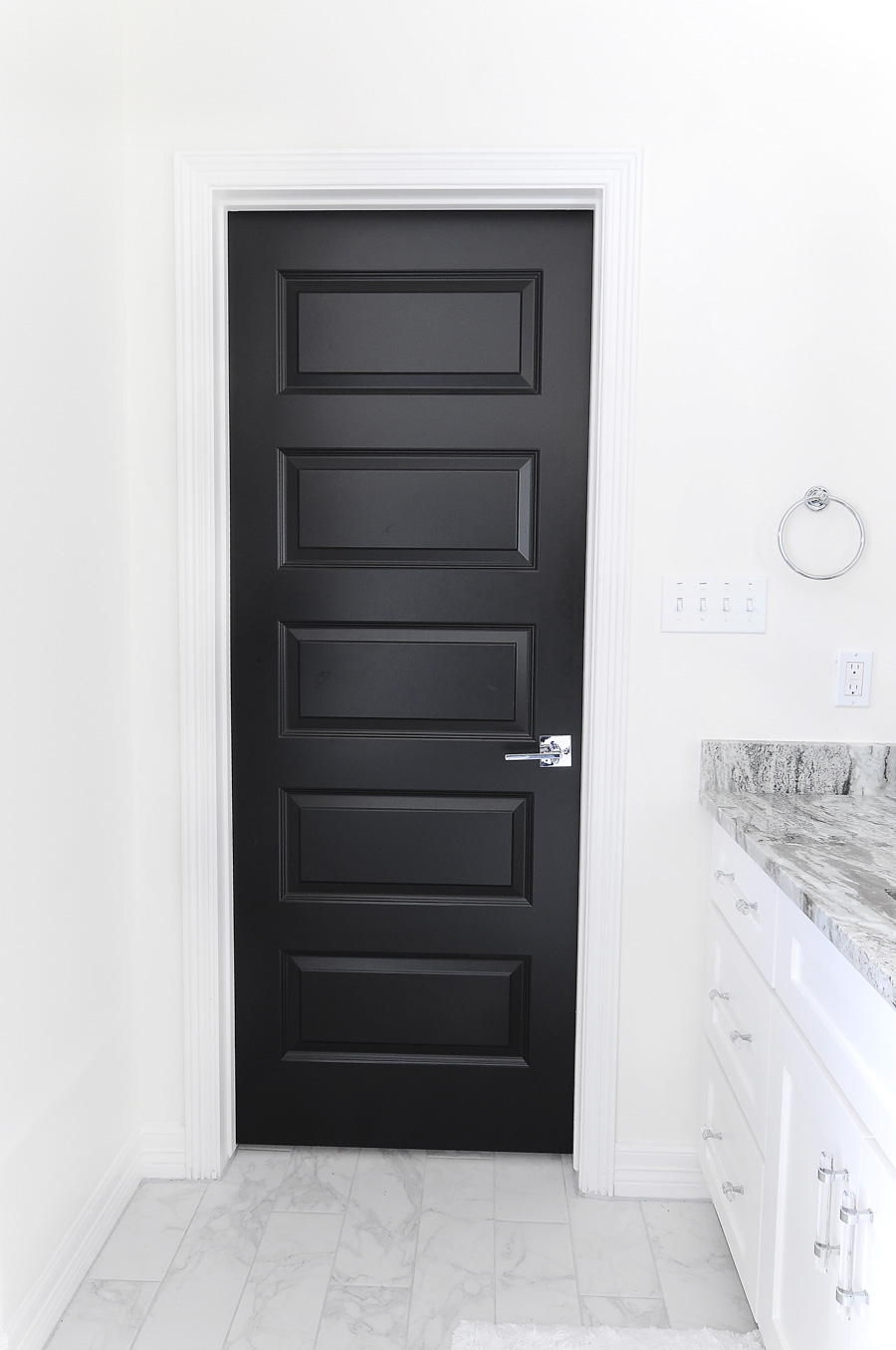 Black interior doors make a bold and dramatic statement in a home against white walls and marble floors.