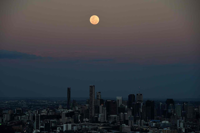 Mặt Trăng mọc cao trên bầu trời thành phố Brisbane, thủ phủ của bang Queensland, đông bắc nước Úc. Hình ảnh: Dan Peled/EPA.
