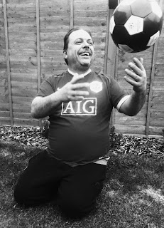 Black and white photo of a man, seated, catching a football