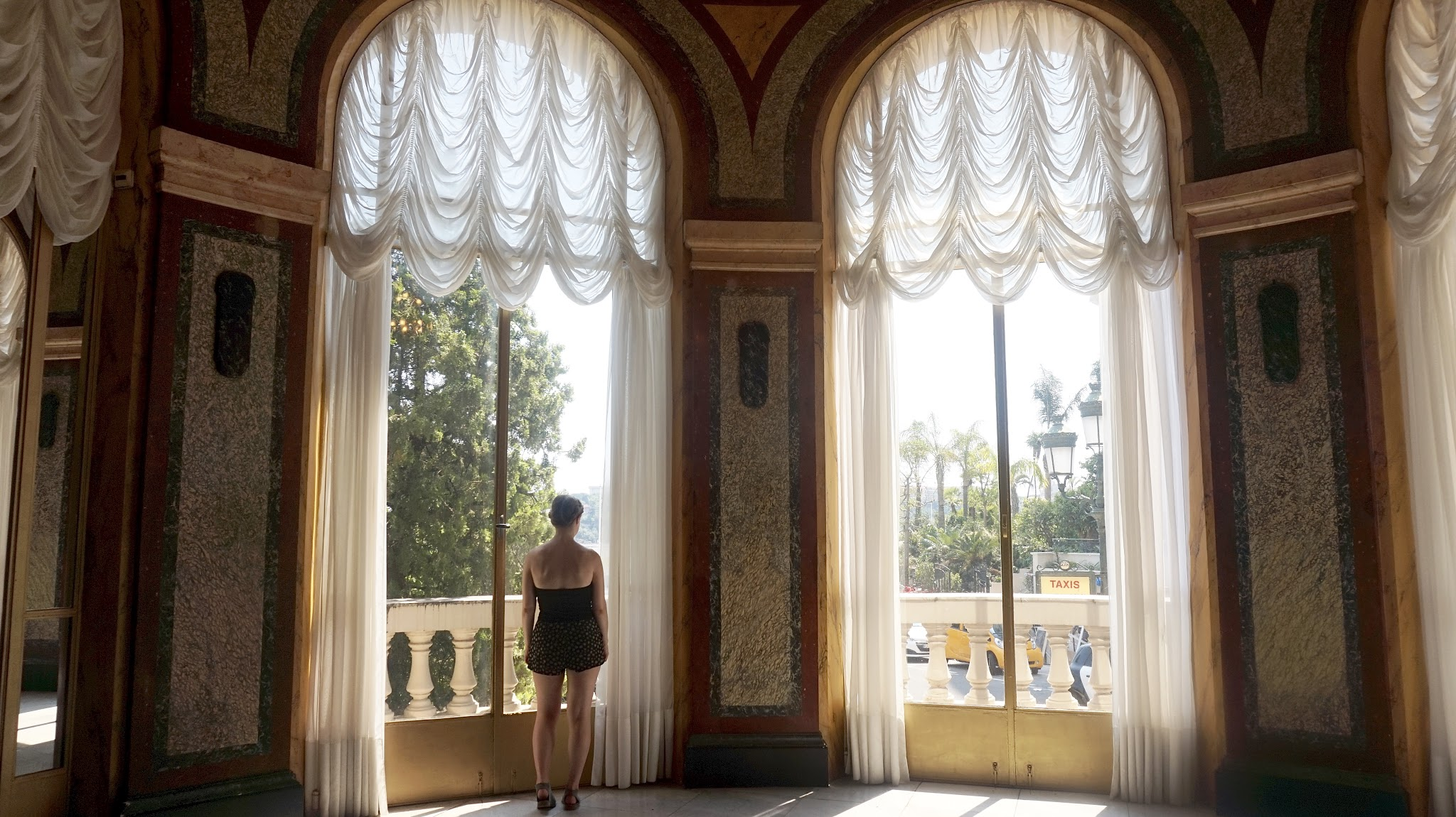woman stood at a tall window with plush net curtains