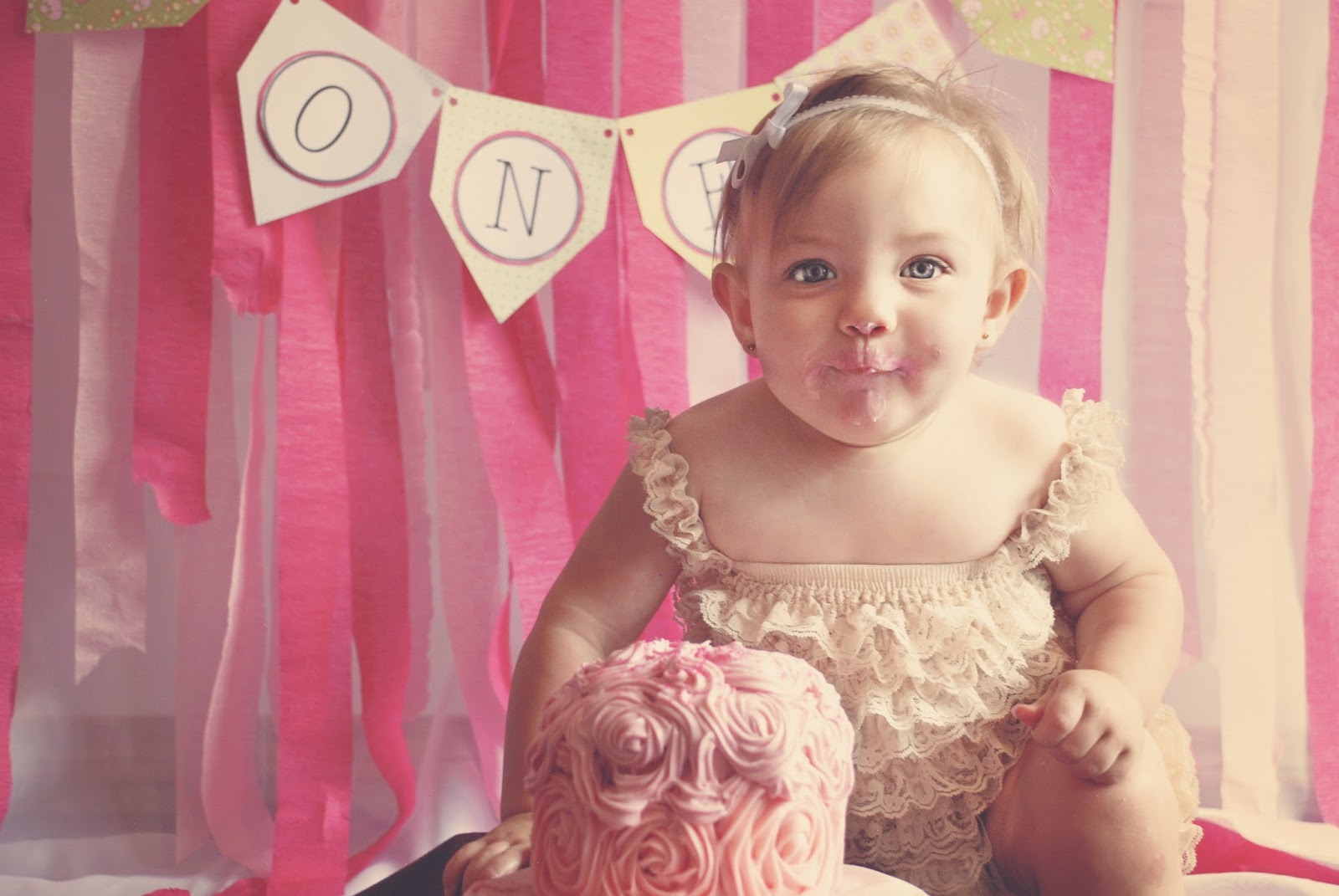 Little girl eating her first birthday cake - cost of children's birthdays - motherdistracted.co.uk
