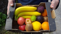 A medium fruit box with banana, apple, plum, kiwi, lemon and lime