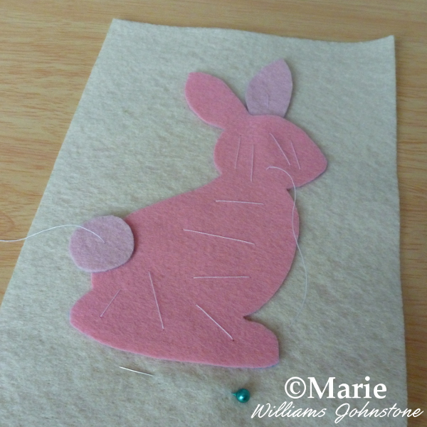 Pink felt Easter bunny rabbit free applique motif hand basted onto cream backing fabric ready to sew