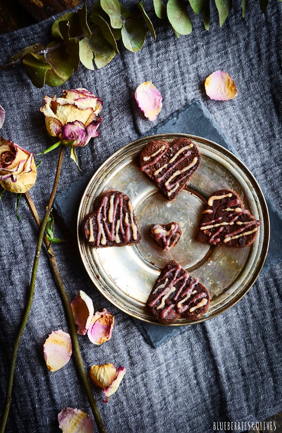 BROWNIE HEARTS IN METALLIC DISH WITH GREY LINEN TABLECLOTH, ROSES, PETALS AND EUCALIPTUS BRANCH