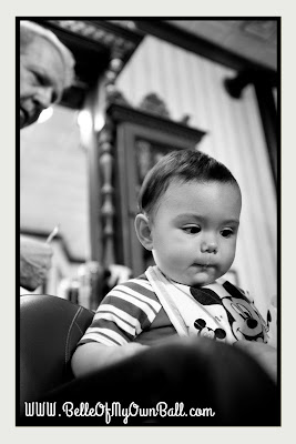 A photo of a baby receiving his first haircut at Harmony Barber Shop in the Magic Kingdom.