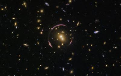 """Các vòng cung bao quanh của hình ảnh này từ Kính viễn vọng Không gian Hubble thực sự là ánh sáng bị bóp méo của các thiên hà xa xôi, để tạo thành một """"vòng Einstein"""" bởi ảnh hưởng hấp dẫn của cụm sao thiên hà gần đó SDSS J0146-0929. Ảnh: ES"""