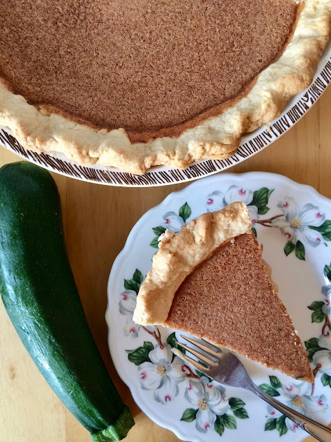 Photo of finished zucchini pie with a slice on a small plate.