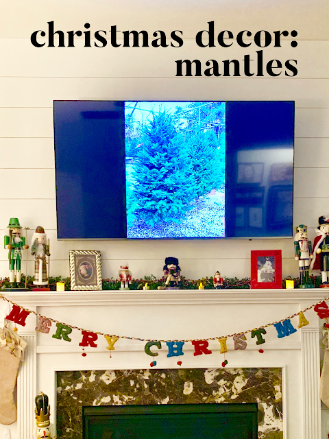 Fireplace mantle decorated with nutcrackers and greenery and a TV showing two christmas trees.