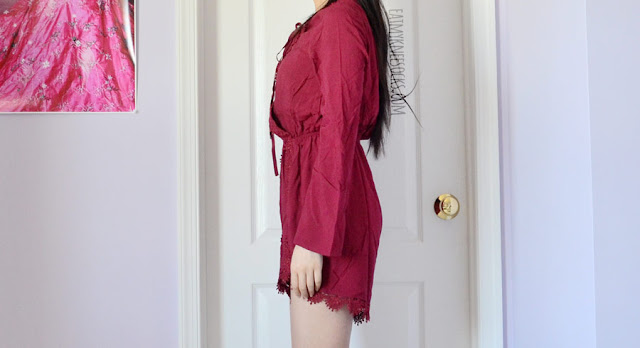 Details on the wine red burgundy long sleeve romper from SheIn, featuring a lace-up plunging front lattice neckline, flared sleeves, and crochet trim.