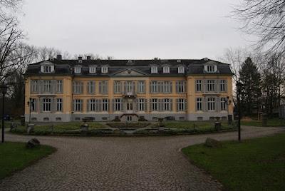 Schloss Morsbroich mit seiner gelben Fassade, einer kleinen Freitreppe und vielen Fenstern