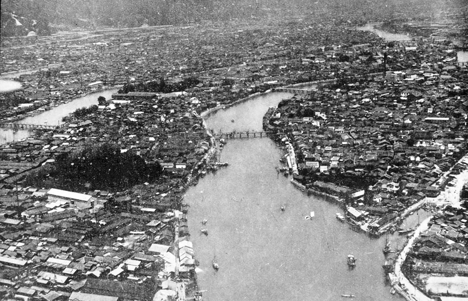 Aerial view of the densely built-up area of Hiroshima along the Motoyasugawa, looking upstream. Except for the very heavy masonry structures, the entire area was devastated. Ground zero of the atomic bomb was upper right in the photo.