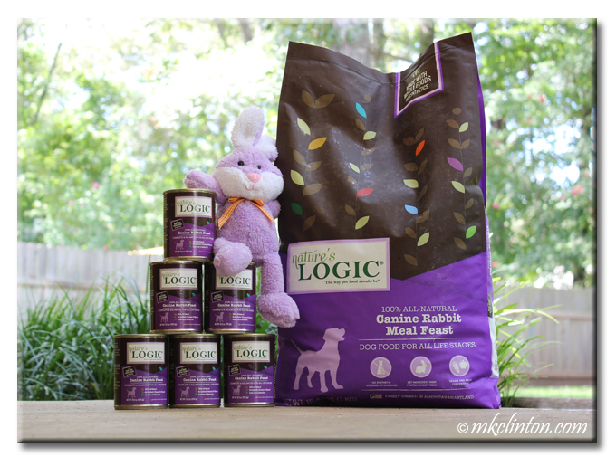 Nature's Logic dog food bag and pyramid of cans with stuffed purple rabbit sitting on cans