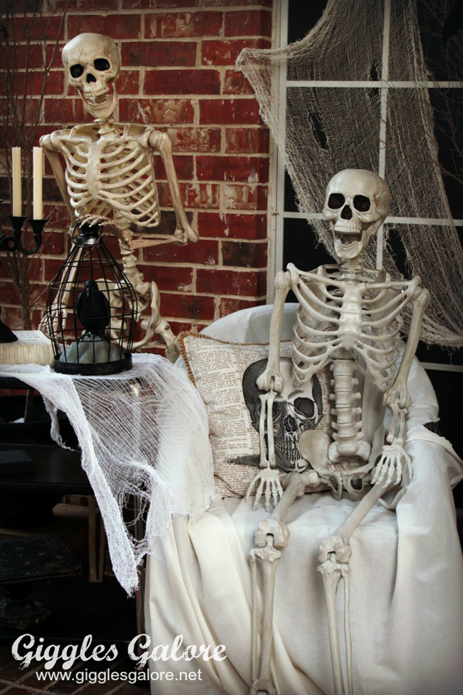 Front porch decorated for Halloween with skeletons sitting on chairs and ghosts standing up