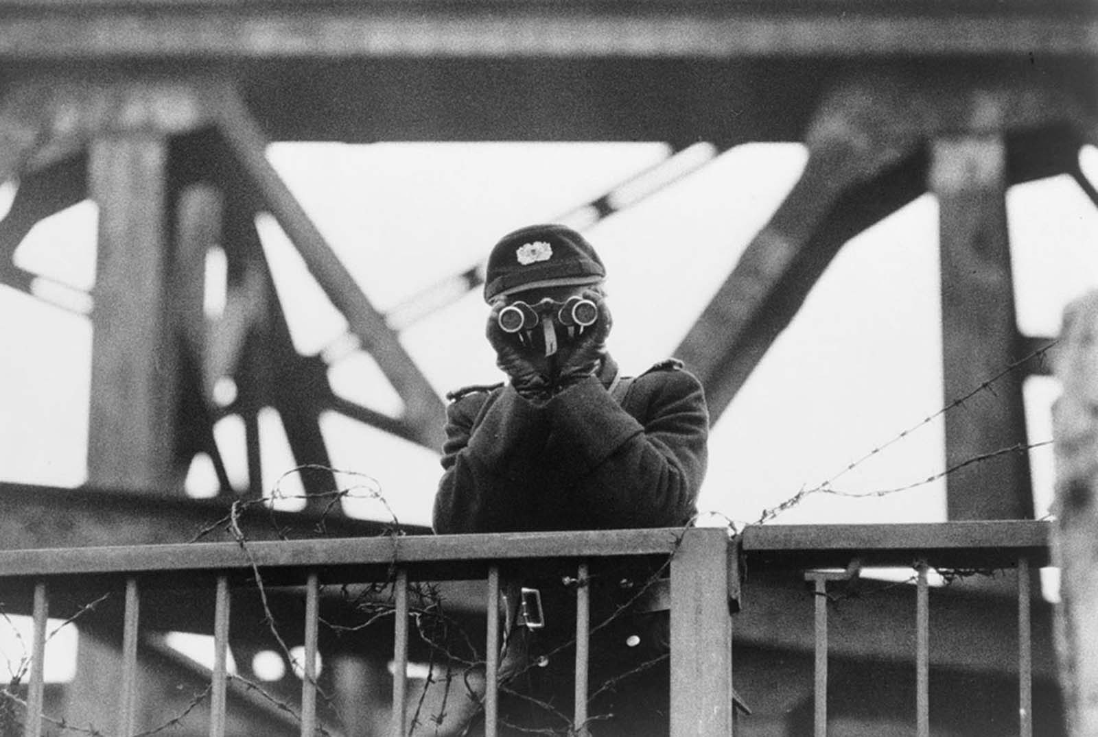 An East German VOPO (Volkspolizei) border policeman uses binoculars while standing guard on one of the bridges linking East and West Berlin, in 1961.