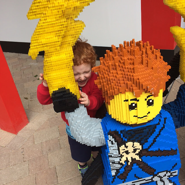 Large lego ninjago figure with little boy smiling behind it