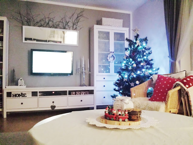 Lustro nad telewizorem i gałęzie z lampkami