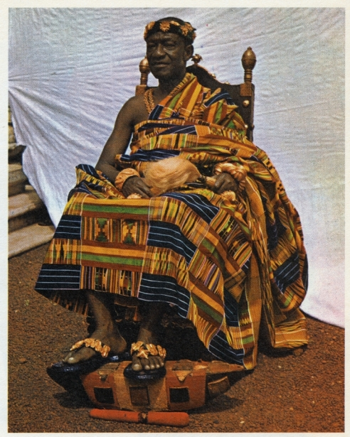 Otumfuo Sir Osei Agyeman Prempeh II, K.B.E. wearing his special regal kente (circa 1930). Asantehene, occupant of the Golden Stool.... He is seated on one of his ceremonial chairs, the ankaahono, decorated with a gold design of sliced oranges
