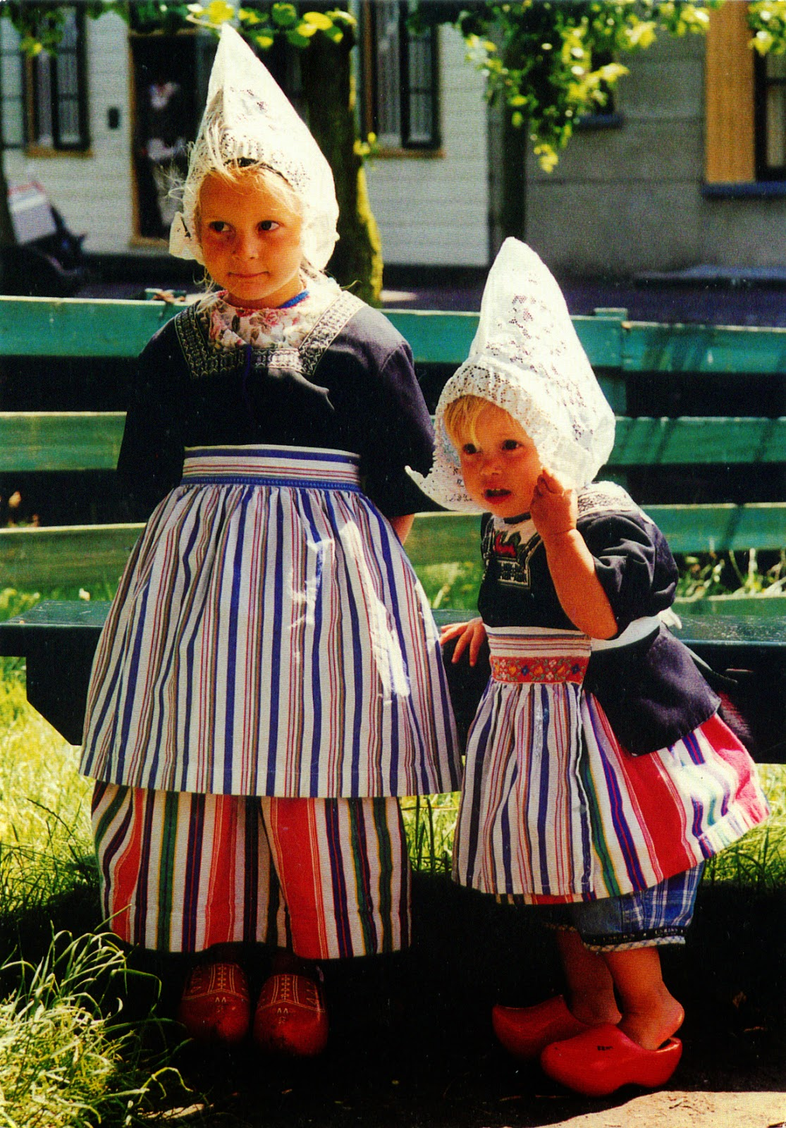 Traditional Netherlands costumes worn by women include ankle-length dresses with long sleeves, aprons and a small fitted cloth hat. Men wear a traditional costume with a long sleeve button up shirt; loose, pleated front pants; neck scarf and hat.