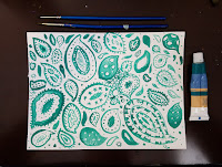 teal painted paisley pattern with 2 paintbrushes above and a paint tube