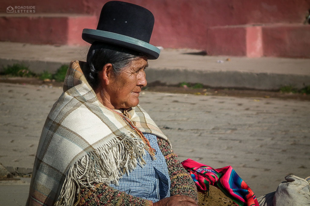 Old indigenous lady waiting for a bus in one of Andean towns